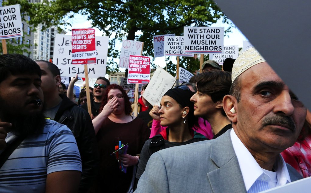 Counterprotesters, including Shahid Haq, right, face City Hall Plaza and March Against Sharia demonstrators. (Alan Berner / The Seattle Times)