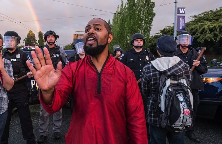 Andrè Taylor — whose brother, Che Taylor, was shot and killed by Seattle police — tells the crowd Tuesday evening that it is the Lyles family's wishes that the protest end for the night, dispersing the crowd. Friends and family of Charleena Lyles gathered to remember her and called for police accountability. (Dean Rutz / The Seattle Times)