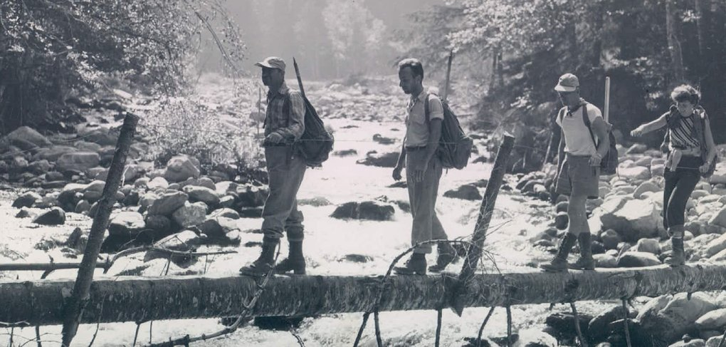 Hikers cross a temporary bridge at Godkin Creek on their way to the Elwha Basin in 1951. (Seattle Times archive)