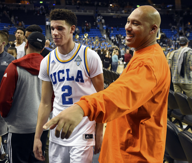 FILE – In this Nov. 20, 2016, file photo, UCLA's Lonzo Ball (2) walks by his father LaVar Ball, right, to greet family members after UCLA defeated Long Beach State in an NCAA college basketball game in Los Angeles.  By now the entire basketball world knows Lonzo Ball is a singular talent with a unique parent.  (AP Photo/Michael Owen Baker, File)