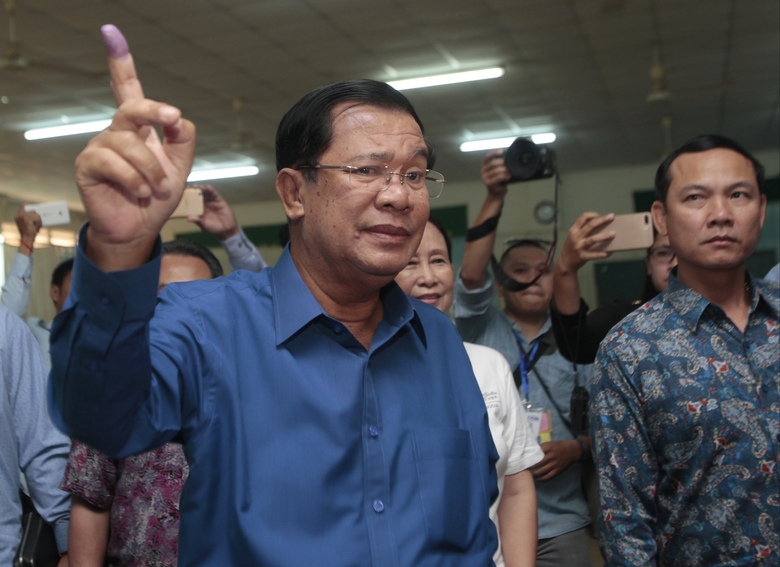 Cambodian Prime Minister Hun Sen of the Cambodian People's Party shows off his inked finger after voting in local elections at Takhmua polling station in Kandal province, southeast of Phnom Penh, Cambodia, Sunday, June 4, 2017. (AP Photo/Heng Sinith)