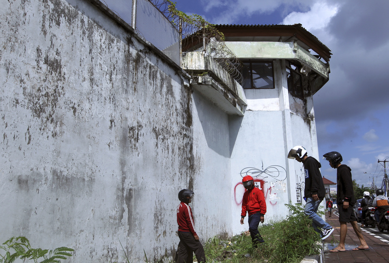 Residents observe a hole on the ground through which four foreign inmates have escaped from Kerobokan prison in Bali, Indonesia, Monday, June 19, 2017. Prison officers became aware of the escape while conducting a morning check of inmates at the Kerobokan penitentiary in Bali's capital, Denpasar, said Putu Ika Prabawa, an officer at Bali's Kuta Utara police station. (AP Photo/Firdia Lisnawati)