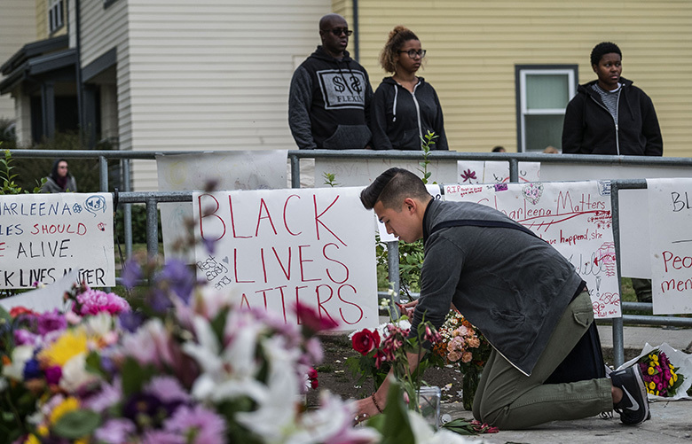 Travis Nguyen puts down flowers at a memorial for Lyles outside her apartment.  Friends and family of Charleena Lyles, shot and killed by Seattle Police last week, had a vigil for her outside the Brettler Family Place Tuesday, June 20, 2017.