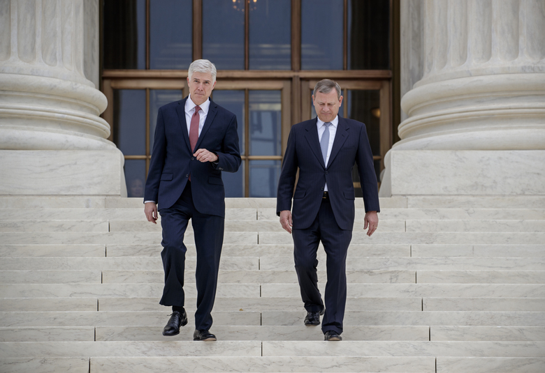Associate Supreme Court Justice Neil Gorsuch left joined by Chief Justice John Roberts walks down the steps of Supreme Court in Washington Thursday