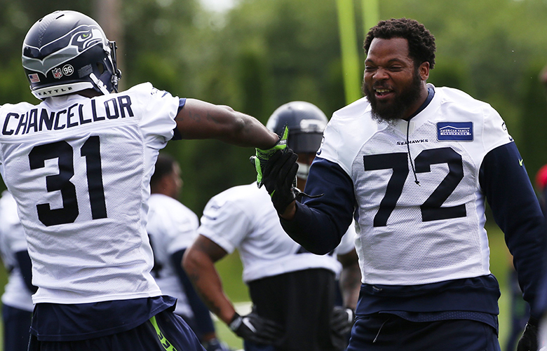 Defensive end Michael Bennett (72) does a dance with strong safety Kam Chancellor (31) during Seahawks minicamp, Wednesday, June 14, 2017, in Renton.