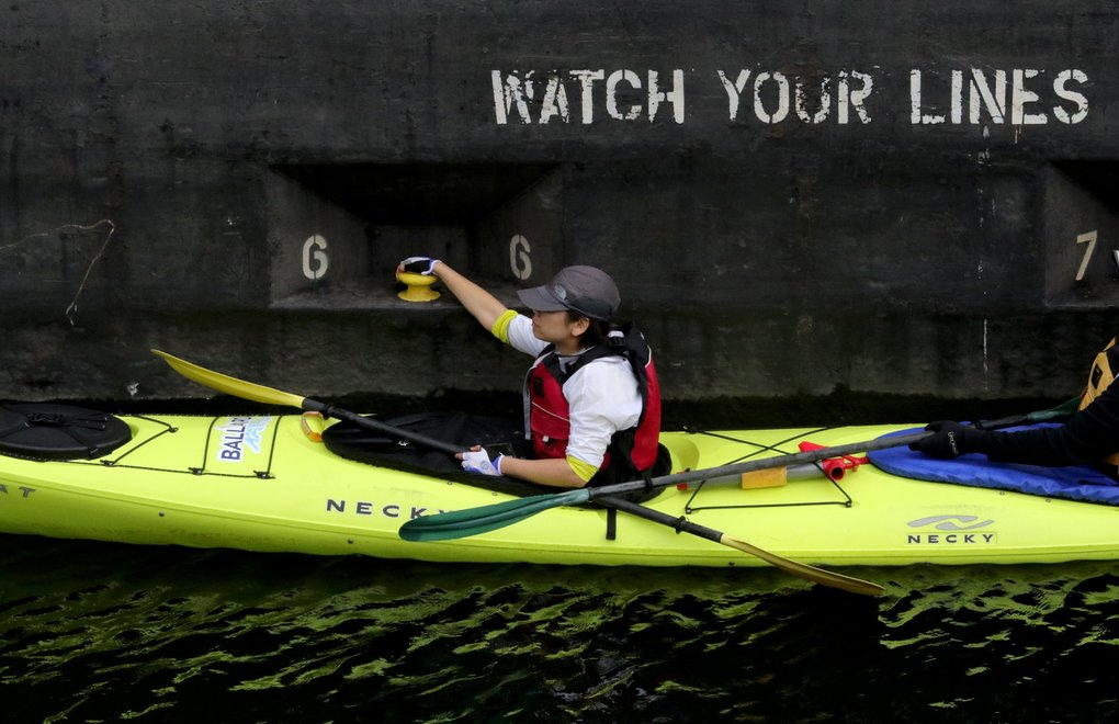 A kayaker in the small lock holds a cleat on the floating wall panel. (Alan Berner/The Seattle Times)