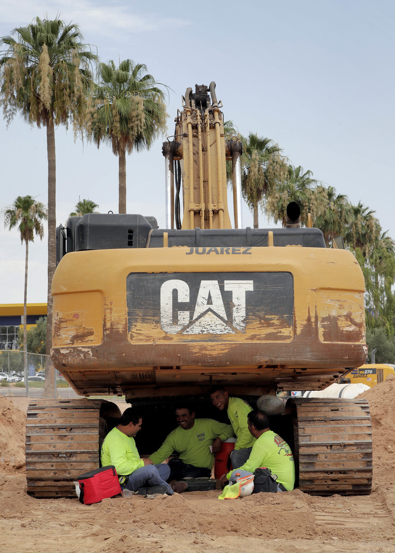 A crew from Juarez Construction sits under their excavator during a break to avoid the heat, Tuesday, June 20, 2017 in Tempe, Ariz. Phoenix hit a high of 118 on Monday with an excessive heat warning in place until Saturday.  (AP Photo/Matt York)