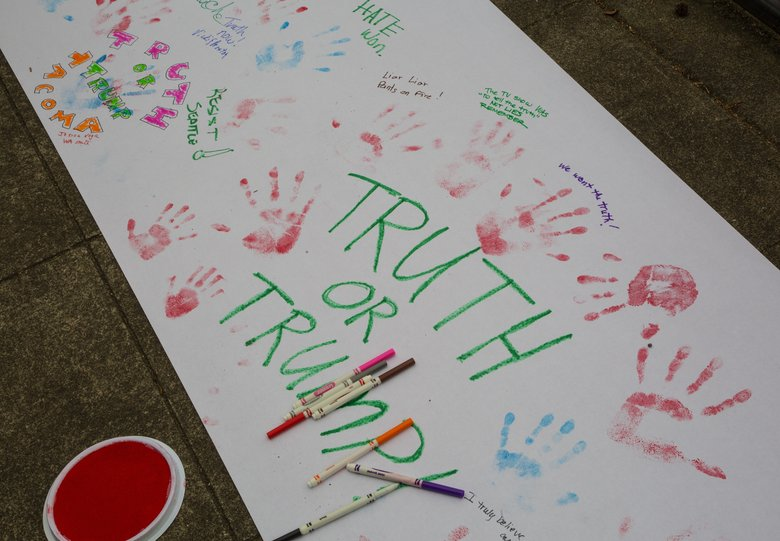 """Several hundred people gathered Saturday morning at Cal Anderson Park on Seattle's Capitol Hill for a """"March for Truth"""" demonstration. The group left handprints and signed messages to the Trump administration on a giant banner that will be delivered to the White House. (Mike Siegel / The Seattle Times)"""