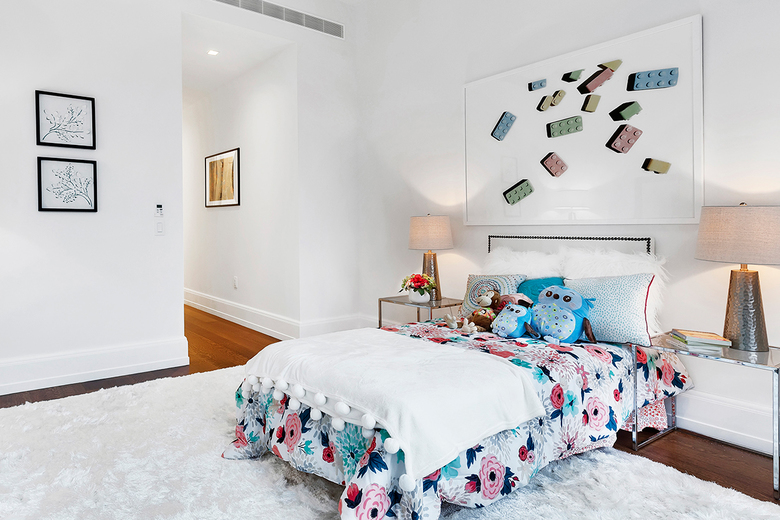 Two smaller pieces of art serve as filler pieces, while an oversize piece appears to serve as a headboard in this children's room. (TNS)