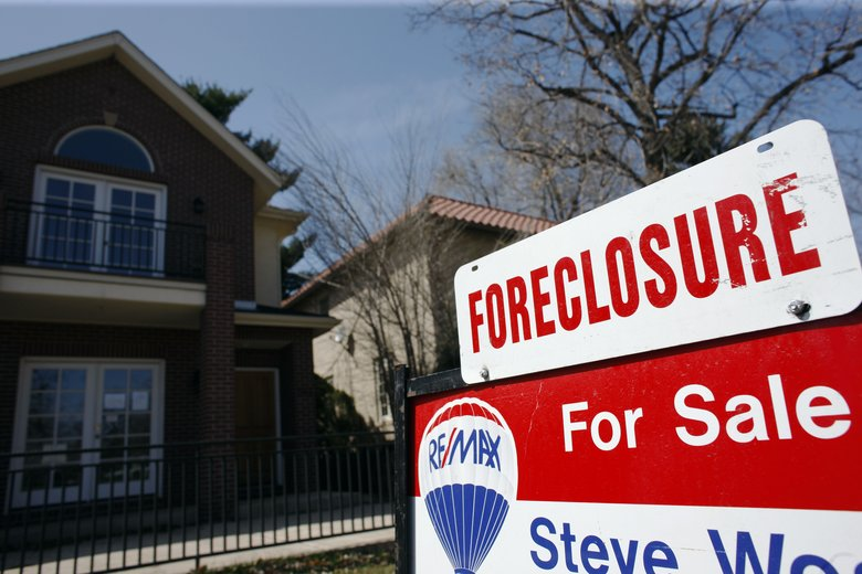 A foreclosure sign atop a for sale sign in Denver. Know the pitfalls to such a purchase, experts urge. (David Zalubowski/The Associated Press)