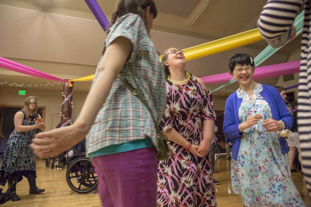Kelley Fox, 23, center, sings and dances with friends May 8 at the Spring Fling, a dance for participants of four local programs for adults with developmental disabilities. She's had two brain surgeries, including a full hemispherectomy, to help with seizures.  (Bettina Hansen/The Seattle Times)