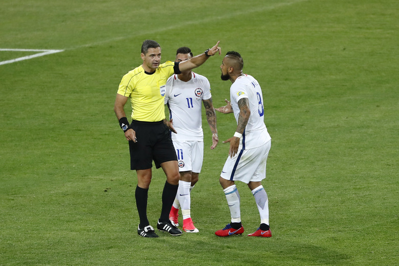 Chile's Arturo Vidal, right, and Eduardo Vargas argue with referee Demir Skomina during the Confederations Cup, Group B soccer match between Cameroon and Chile, at the Spartak Stadium in Moscow, Sunday, June 18, 2017. (AP Photo/Alexander Zemlianichenko)