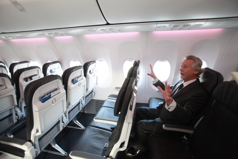 Blake Emery, who headed interior cabin redesigns at Boeing, inside the passenger cabin of a Boeing 737-900ER . The issue of passenger legroom has boiled over as some carriers consider adding more seats.  (Ken Lambert/The Seattle Times)