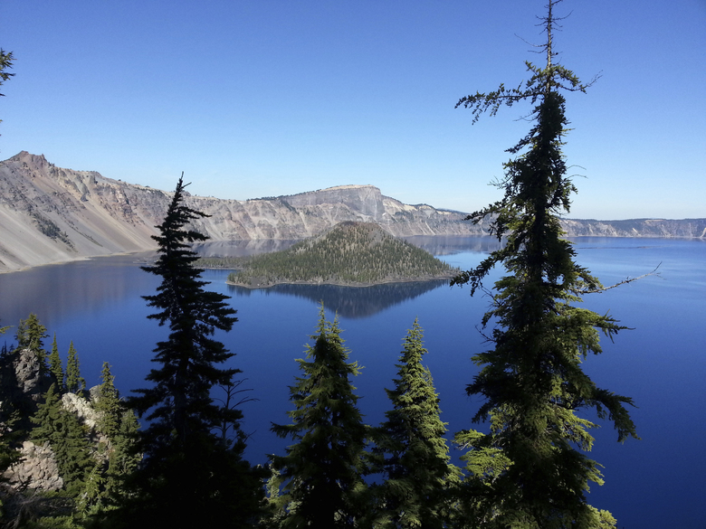 FILE – This Oct. 5, 2015, file photo shows Wizard Island in Crater Lake from the rim trail between Rim Village and Watchman Peak at Crater Lake, Ore. A 20-year-old man died Tuesday, July 4, 2017, at Crater Lake National Park after falling from a cliff ledge into Crater Lake's caldera. (David Smigelski /The Medford Mail Tribune via AP, File)