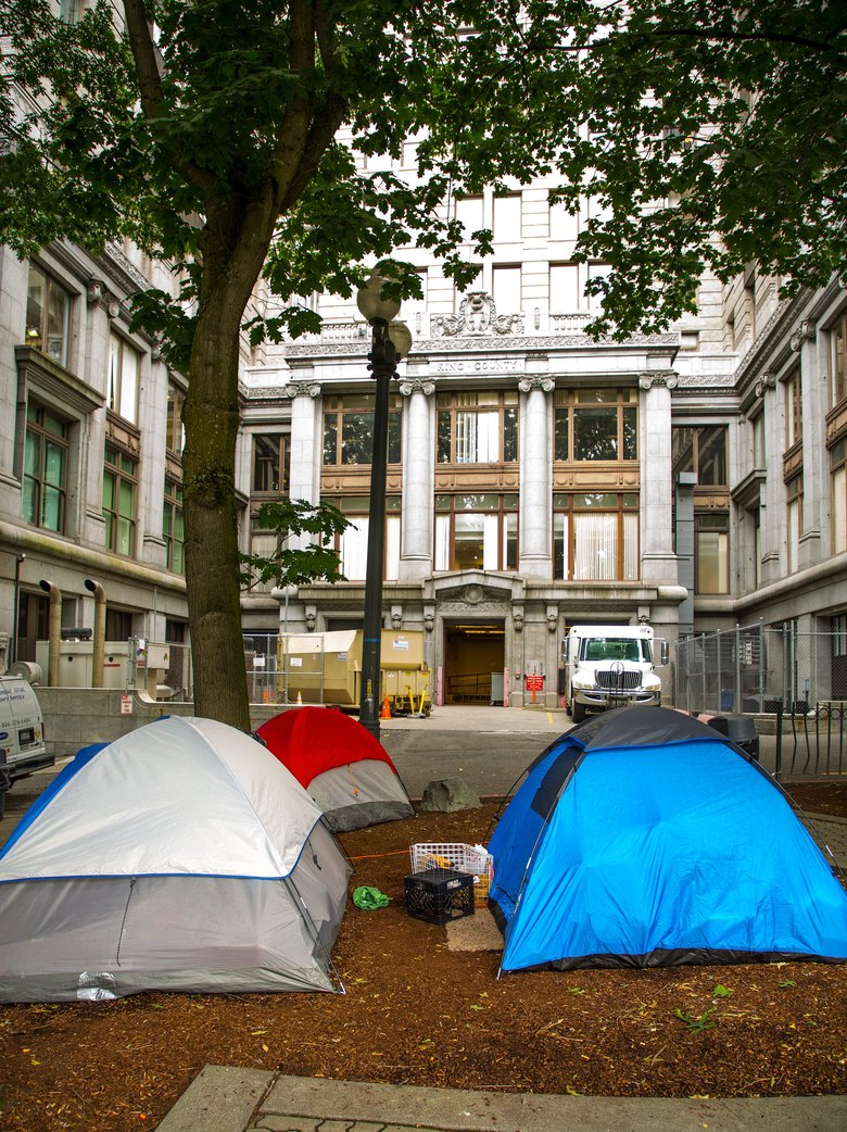 Tents for the homeless are set up in City Hall Park just south of the King County Courthouse. The County Council on Tuesday heard concerns about both cleanliness and security around the courthouse. Jurors and courthouse personnel have reported being assaulted when entering or leaving the courthouse. (Mike Siegel/The Seattle Times)