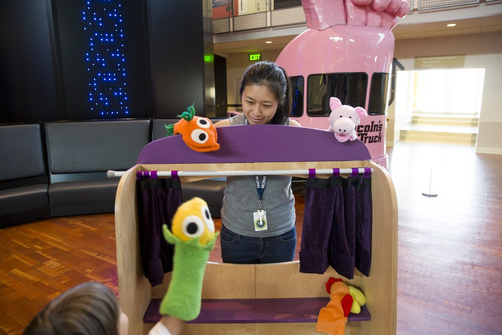 At MOHAI, you can play with your food. Here, Anna Cheung, a K-12 and youth programs assistant educator, and a guest play with food-themed hand puppets on Monday. (Bettina Hansen/The Seattle Times)