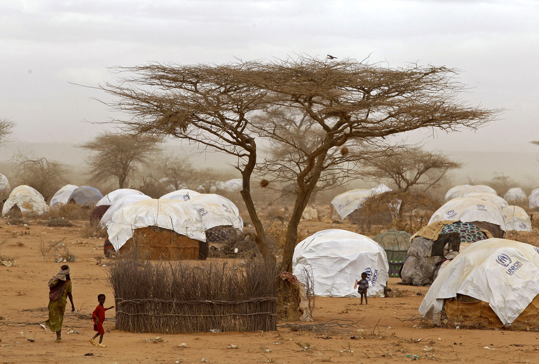 FILE – In this Aug. 4, 2011 file photo, refugees walk amongst huts at a refugee camp in Dadaab, Kenya. Earlier  in 2017, some Somali refugees whose resettlement in the United States was stopped by President Donald Trump's executive order were sent back to the Dadaab refugee camp in northern Kenya. A federal judge in Hawaii further weakened the already-diluted travel ban in a ruling Thursday, July 13, 2017, by vastly expanding the list of U.S. family relationships that visitors from six Muslim-majority countries, Syria, Sudan, Somalia, Libya, Iran and Yemen, can use to get into the country. (AP Photo/Schalk van Zuydam, File)