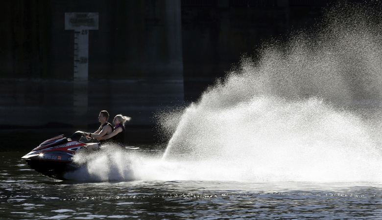 A couple on a personal watercraft head upstream on the Willamette River in downtown Portland.  (Don Ryan/AP)