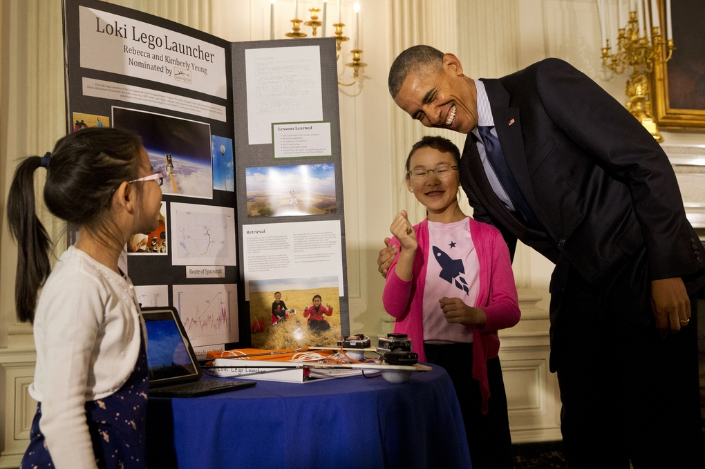 President Obama laughs as he hugs Rebecca Yeung, 11, from Seattle, next to her sister Kimberly Yeung, 9, as they show him their balloon-borne craft at last year's White House Science Fair. In August, the sisters, now 12 and 10, will participate in a citizen science project to study the solar eclipse.(Jacquelyn Martin/The Associated Press. File)