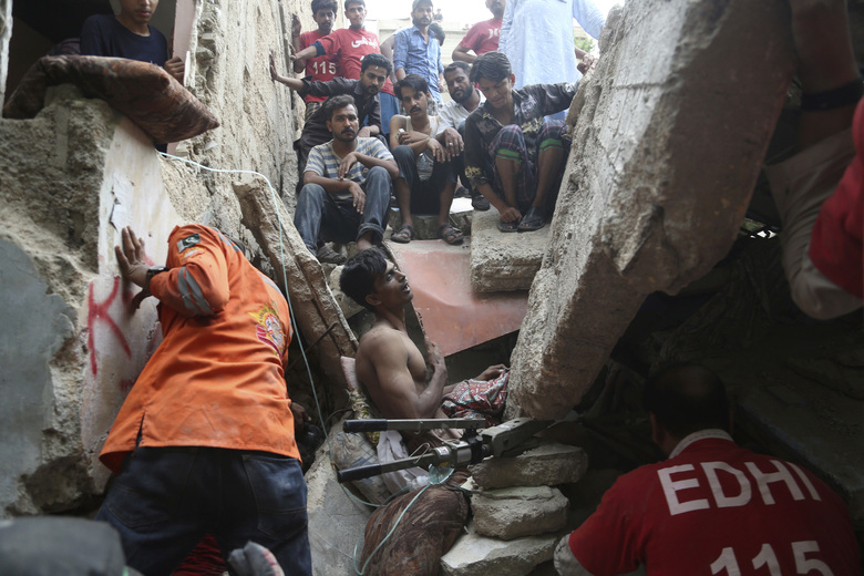 Pakistani volunteers try to rescue a trapped resident in Karachi, Pakistan, Tuesday, July 18, 2017. A dilapidated, three-story building in a poorer neighborhood of Pakistan's sprawling port city of Karachi collapsed as the residents slept. (AP Photo/Shakil Adil)