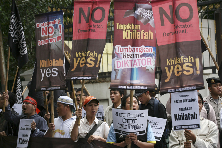 """FILE – In this Feb. 8, 2011 file photo, members of Hizbut Tahrir Indonesia hold posters during a rally in Jakarta, Indonesia. The Indonesian government on Wednesday, July 19, 2017 banned Hizbut Tahrir, an organization that wants to establish a global caliphate, under a new presidential decree criticized as draconian by rights groups. Writings on the posters read """"No to dictatorship or democracy, Yes to caliphate"""" and """"Overthrow dictatorship, uphold the caliphate."""" (AP Photo/Achmad Ibrahim, File)"""