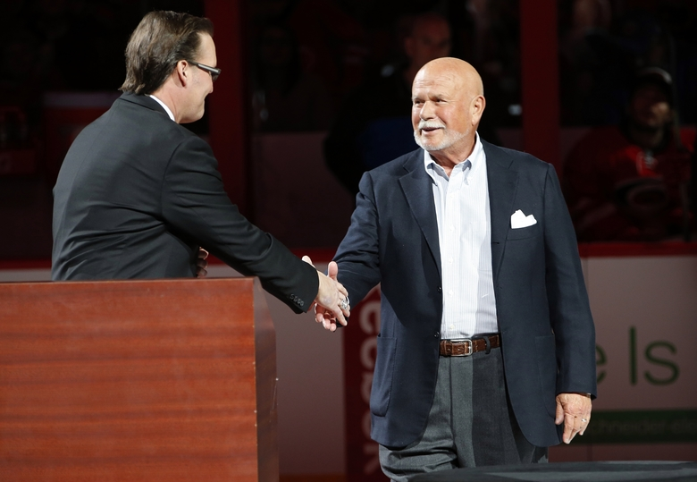 "FILE – In this Feb. 13, 2016, file photo, Carolina Hurricanes broadcaster John Forslund greets Hurricanes owner Peter Karmanos Jr., right, before the teams' NHL hockey game against the New York Islanders in Raleigh, N.C. Karmanos is considering an offer from someone who wants to purchase the team. Spokesman Mike Sundheim said in a statement attributed to the team that Karmanos ""also will continue to evaluate his other options, including retaining his ownership of the team."" (AP Photo/Karl B DeBlaker, File)"