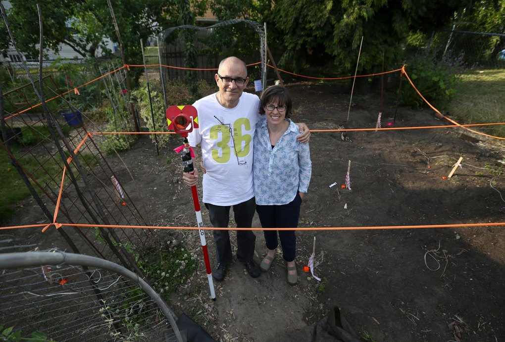 Kim Sherman and Dan Tenenbaum pose in their Beacon Hill backyard with a survey device left behind by workers. They're having a tiny house built in their backyard for a homeless man, through the BLOCK project. (Ken Lambert/The Seattle Times)