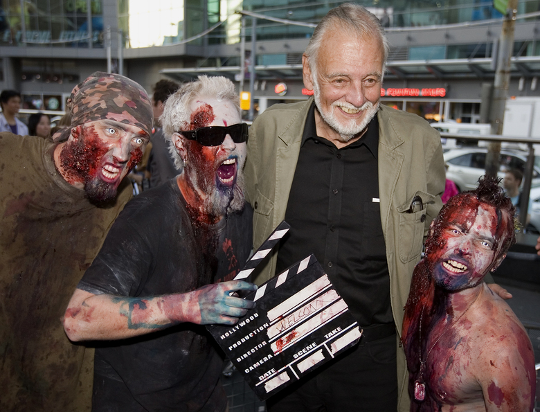 "FILE – In this Sept. 12, 2009, file photo, director George Romero poses with some fans dressed as zombies after accepting a special award during the Toronto International Film Festival in Toronto. Romero, whose classic ""Night of the Living Dead"" and other horror films turned zombie movies into social commentaries and who saw his flesh-devouring undead spawn countless imitators, remakes and homages, has died. He was 77. Romero died Sunday, July 16, 2017, following a battle with lung cancer, said his family in a statement provided by his manager Chris Roe. (Darren Calabrese/The Canadian Press via AP, File)"