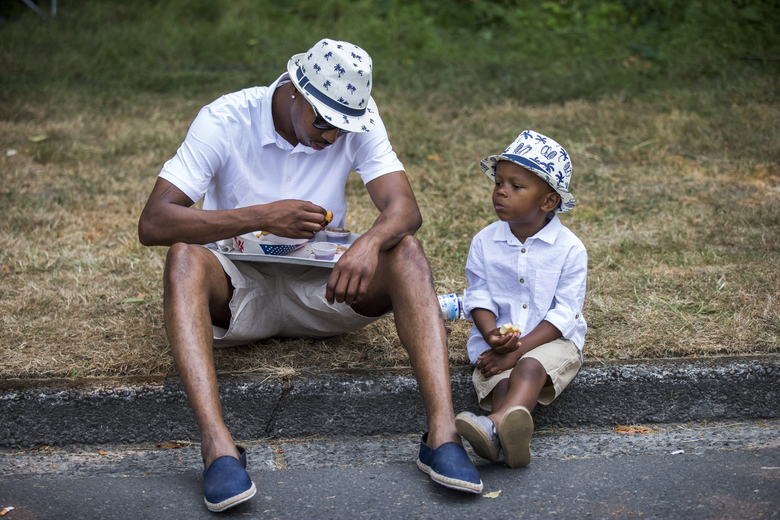 Anthony Lamar Perry Senior, left, eats with son Anthony Lamar Perry Junior, right, while watching the hydro race on Sunday, August 6, 2017 on Lake Washington. (Kjell Redal/The Seattle Times)