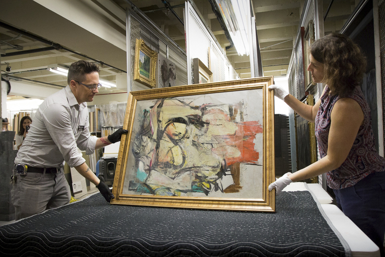 "In this Aug. 9, 2017 photo provided by the University of Arizona, Willem de Kooning's ""Woman-Ochre""  is readied for examination by Nathan Saxton, right, an exhibitions specialist, and Kristen Schmidt, a registrar, in Phoenix. More than three decades after thieves made off with the valuable painting from the University of Arizona Museum of Art, officials have recovered the long sought piece from an antique dealer in New Mexico.  (University of Arizona via AP)"
