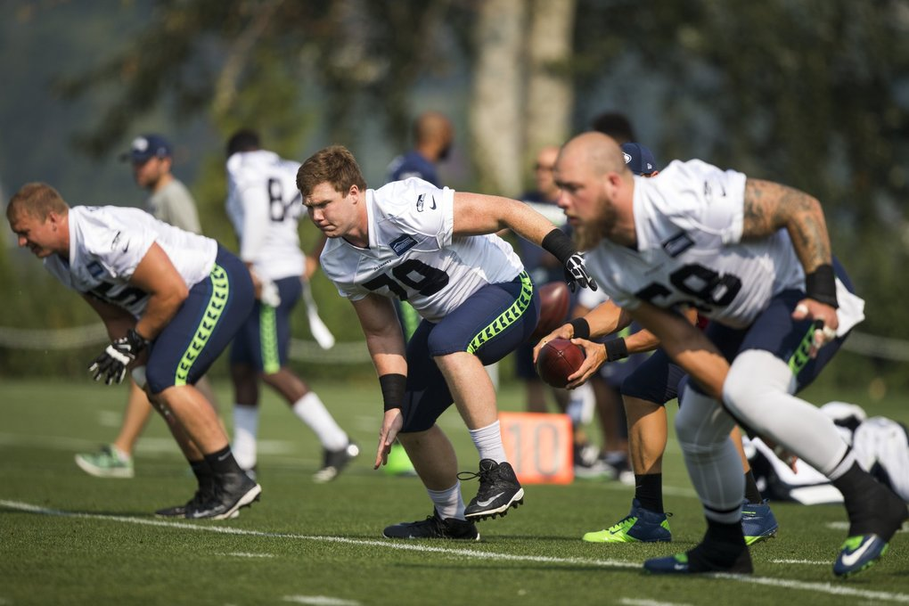 From left, Will Pericak, Ethan Pocic, and Justin Britt, practice at center at Seattle Seahawks Training Camp. (Bettina Hansen / The Seattle Times)