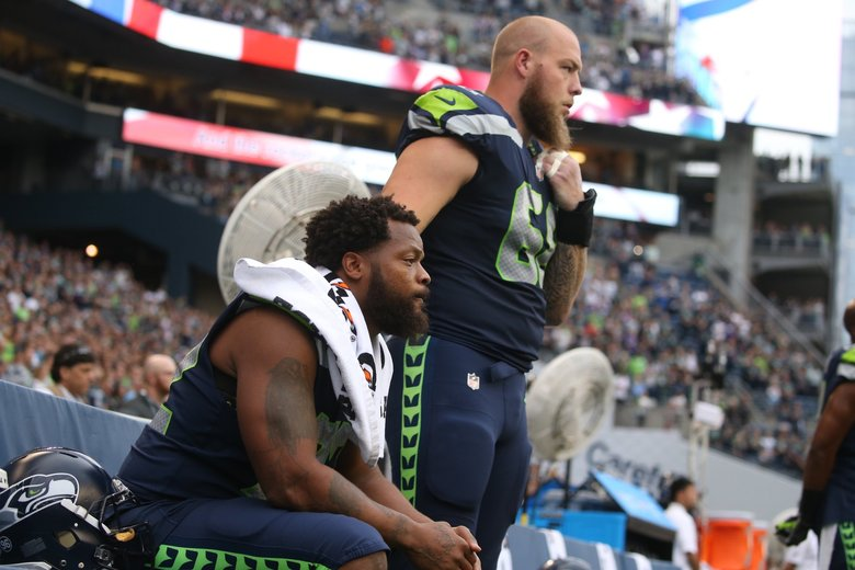 Michael Bennett sits for the national anthem with Justin Britt standing beside him as the Seattle Seahawks take on the Minnesota Vikings for a preseason game at CenturyLink Field in Seattle Friday. (Bettina Hansen / The Seattle Times)
