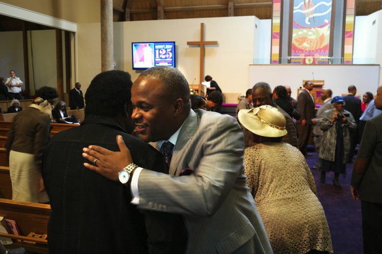 The Rev. Aaron Williams, center, greets parishioners during a 2015 service celebrating the 125th anniversary of Mount Zion Baptist Church. (John Lok / The Seattle Times, file)