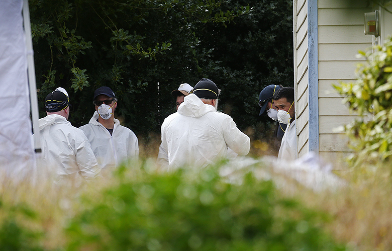 Police investigate the home where three elderly brothers were charged with child-exploitation, Wed., Aug. 23, 2017, in Seattle.