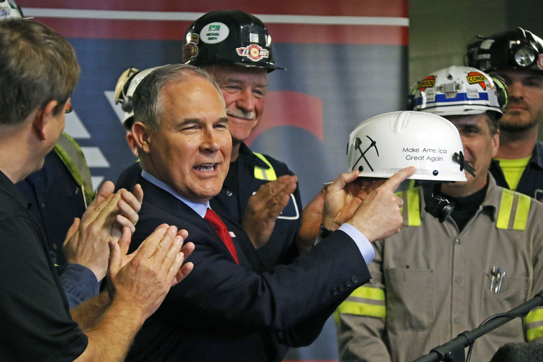 "FILE – In this April 13, 2017, file photo, Environmental Protection Agency Administrator Scott Pruitt holds up a hardhat he was given during a visit to Consol Pennsylvania Coal Company's Harvey Mine in Sycamore, Pa. As President Donald Trump touts new oil pipelines and pledges to revive the nation's struggling coal mines, federal scientists are warning that burning fossil fuels is already driving a steep increase in the United States of heat waves, droughts and floods. Faced with reams of evidence complied by federal scientists that conflicts with their policy positions, Trump and his advisers frequently cite the work of industry-funded think tanks. Pruitt and Energy Secretary Rick Perry have championed the formation of a ""red-team, blue-team"" exercise where climate-change skeptics would publicly debate mainstream climate scientists.(AP Photo/Gene J. Puskar, File)"