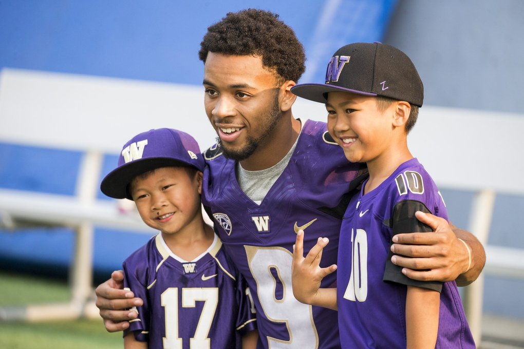 Tailback Myles Gaskin takes a picture with Kasen Fernando, 5, left, and his brother  Nathan, 9, right, on the field for picture day, an annual training camp tradition for the University of Washington Huskies football team at Husky Stadium Sunday August 6, 2017. Mom Corey Fernando said that Kasen is named after the former UW wide receiver, and met the star player when he was just a newborn.   (Bettina Hansen / The Seattle Times)