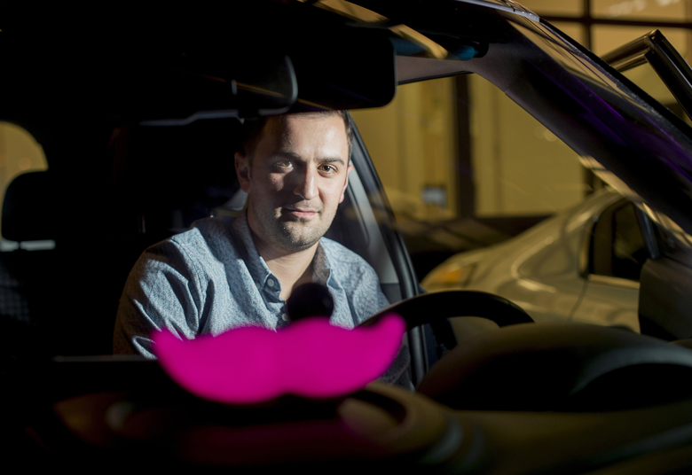 """FILE – In this Jan. 26, 2015, file photo, Lyft co-founder John Zimmer displays his company's """"glowstache"""" following a launch event in San Francisco. When management upheaval, allegations of corporate espionage, and revelations of sexual harassment sent Uber into a public relations sinkhole, its long overshadowed rival Lyft shifted into overdrive. The company seized the opportunity to recruit disillusioned drivers so it could be more responsive to passengers searching for a ride-hailing alternative to Uber. After five years of being content in its role as the underdog of ride hailing, Lyft is proving to be a more imposing threat to Uber. (AP Photo/Noah Berger, File)"""