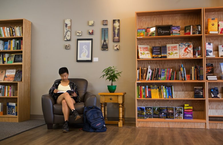 Jing Jing Wang, of Redmond, reads a new book at Brick & Mortar Books on Aug. 1. It was her birthday and she said that her gift for herself was to read all day long at the store. (Ellen M. Banner/The Seattle Times)