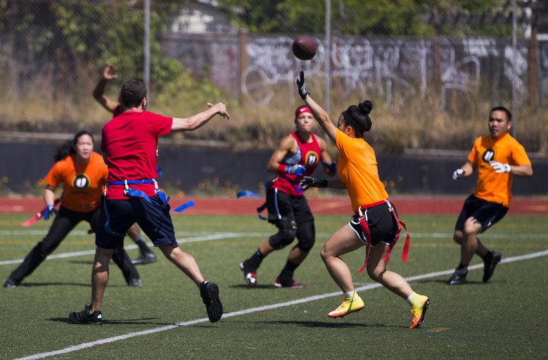 Practice All-Americans tries to move the ball against the defense of Malicious in a flag football game. (Kjell Redal/The Seattle Times)