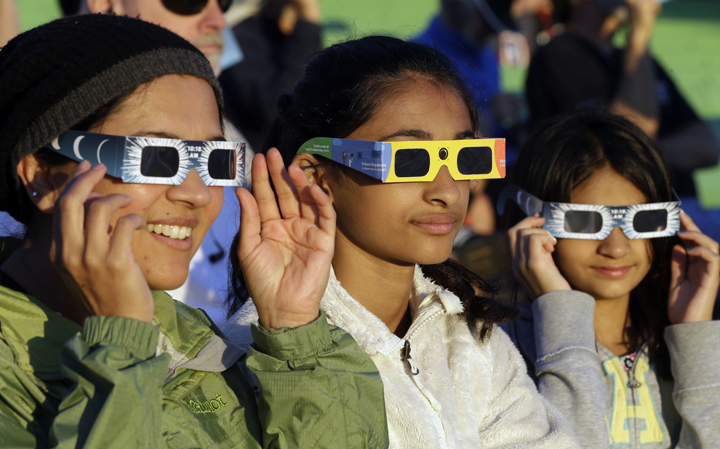 Schweta Kulkarni, from left, Rhea Kulkarni and Saanvi Kulkarni, from Seattle, try out their eclipse glasses on the sun at a gathering of eclipse viewers in Salem, Ore., early Monday. (AP Photo/Don Ryan)