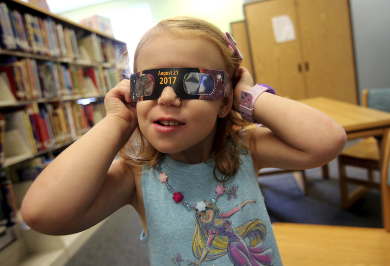 FILE – In this Wednesday, Aug. 2, 2017 file photo, Emmalyn Johnson, 3, tries on her free pair of eclipse glasses at Mauney Memorial Library in Kings Mountain, N.C. Glasses are being given away at the library for free while supplies last ahead of the big event on Aug. 21. (Brittany Randolph/The Star via AP)