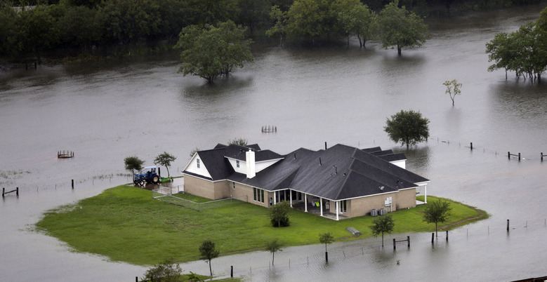 A home is surrounded by floodwaters from Tropical Storm Harvey on Tuesday, Aug. 29, 2017, in Houston. With its flood defenses strained, the crippled city of Houston anxiously watched dams and levees Tuesday to see if they would hold until the rain stops, and meteorologists offered the first reason for hope – a forecast with less than an inch of rain and even a chance for sunshine. (AP Photo/David J. Phillip)