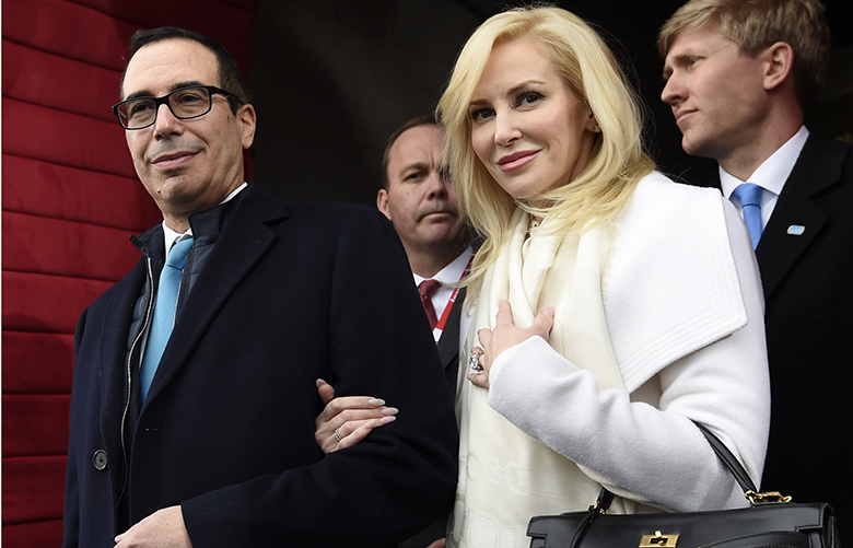 "FILE – In this Friday, Jan. 20, 2017, file photo, then Treasury Secretary-designate Stephen Mnuchin and his then-fiancee, Louise Linton, arrive on Capitol Hill in Washington, for the presidential inauguration of Donald Trump. Linton responded to a social media critic on Aug. 21, 2017, telling the mother of three that that she was ""adorably out of touch."" Mnuchin and Linton were married in June. (Saul Loeb/Pool Photo via AP, File)"