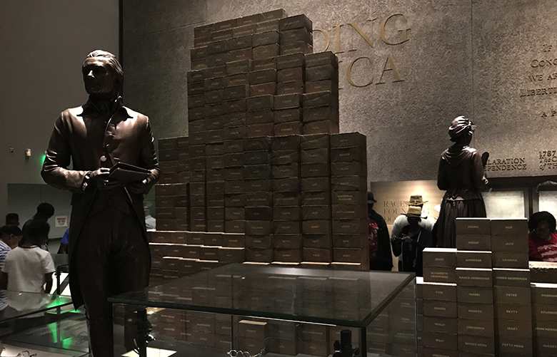 At the National Museum of African American History and Culture, a statue of Thomas Jefferson stands in front of a wall of bricks representing the hundreds of slaves he owned.