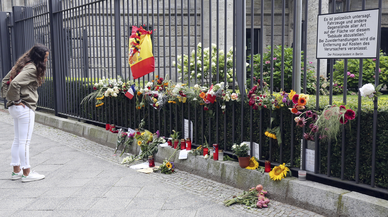A woman looks at the symbols of condolence people have laid down for the victims of the terror attacks that killed 14 people and wounded over 120 in Barcelona , Spain, in front of the Spanish embassy in Berlin, Germany, Monday, Aug. 21, 2017.  (Wolfgang Kumm/dpa via AP)