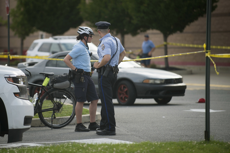 Officers stand near the crime scene of a shooting outside a Target store in Philadelphia, Friday, Aug. 11, 2017. (Cameron B. Pollack/The Philadelphia Inquirer via AP)