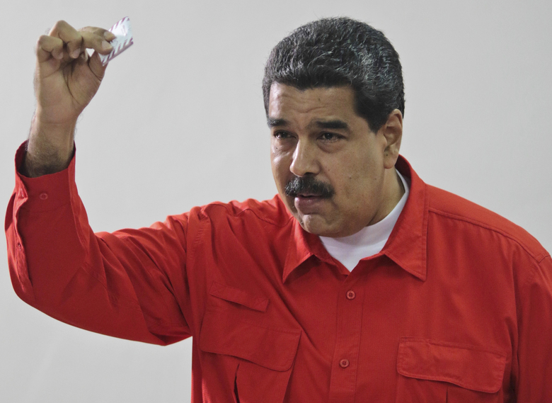 FILE – In this July 30, 2017 file photo, released by the Miraflores Press Office, Venezuela's President Nicolas Maduro shows his ballot after casting a vote for a constitutional assembly in Caracas, Venezuela. With the installation on Friday, Aug. 4, of Venezuela's newly elected, all-powerful constituent assembly, President Maduro's foes fear the body that will write a new constitution is going to entrench the socialist administration and create a one-party state.(Miraflores Press Office via AP, File)