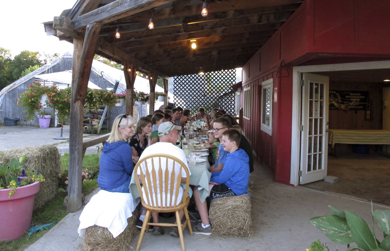 In this Aug. 1, 2017 photo, diners attend a weekly farm dinner at Valley Dream Farm in Cambridge, Vt., featuring produce from the farm and other Vermont made products.  From California to food-loving Vermont, farmers are drawing customers to feast on foods raised in nearby fields. (AP Photo/Lisa Rathke)
