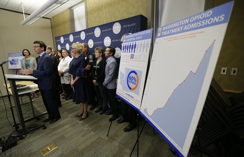 Washington Attorney General Bob Ferguson, second from left, stands near a chart detailing the increase of admissions for opioid addiction treatment in the state. The state and the city of Seattle Thursday filed lawsuits against several makers of opioids.  (AP Photo / Ted S. Warren)