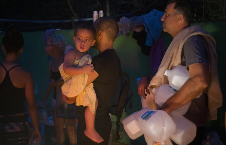 CORRECTS FIRST REFERENCE OF HURRICANE MARIA – People affected by Hurricane Maria collect water in the mountains in Naranjito, Puerto Rico, Wednesday, Sept. 27, 2017.  The relief effort from Hurricane Maria in Puerto Rico has so far been concentrated largely in San Juan, and many outside the capital say they've received little or no help. (AP Photo/Ramon Espinosa) XRE121 XRE121